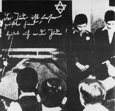 Ca. 1935: Two Jewish pupils are humiliated before their classmates. The inscription on the blackboard reads